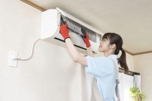 エアコンの清掃をする女性