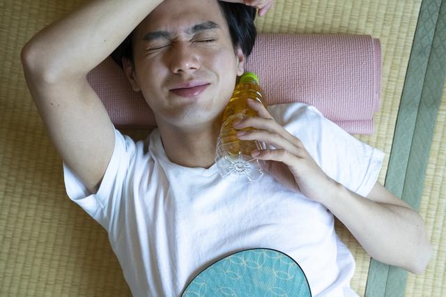 暑い日に部屋でお茶を飲む男性